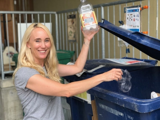 Kelly Rankich holds up a recyclable container at the 21 Acres waste stream.