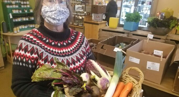 Mary King, masked, holds vegetables that could be used in kitchen stock at the 21 Acres market.