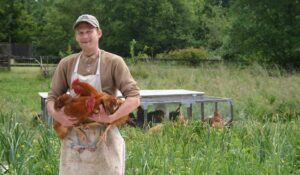 Daniel from Hawthorn Farm holds backyard raised chickens.