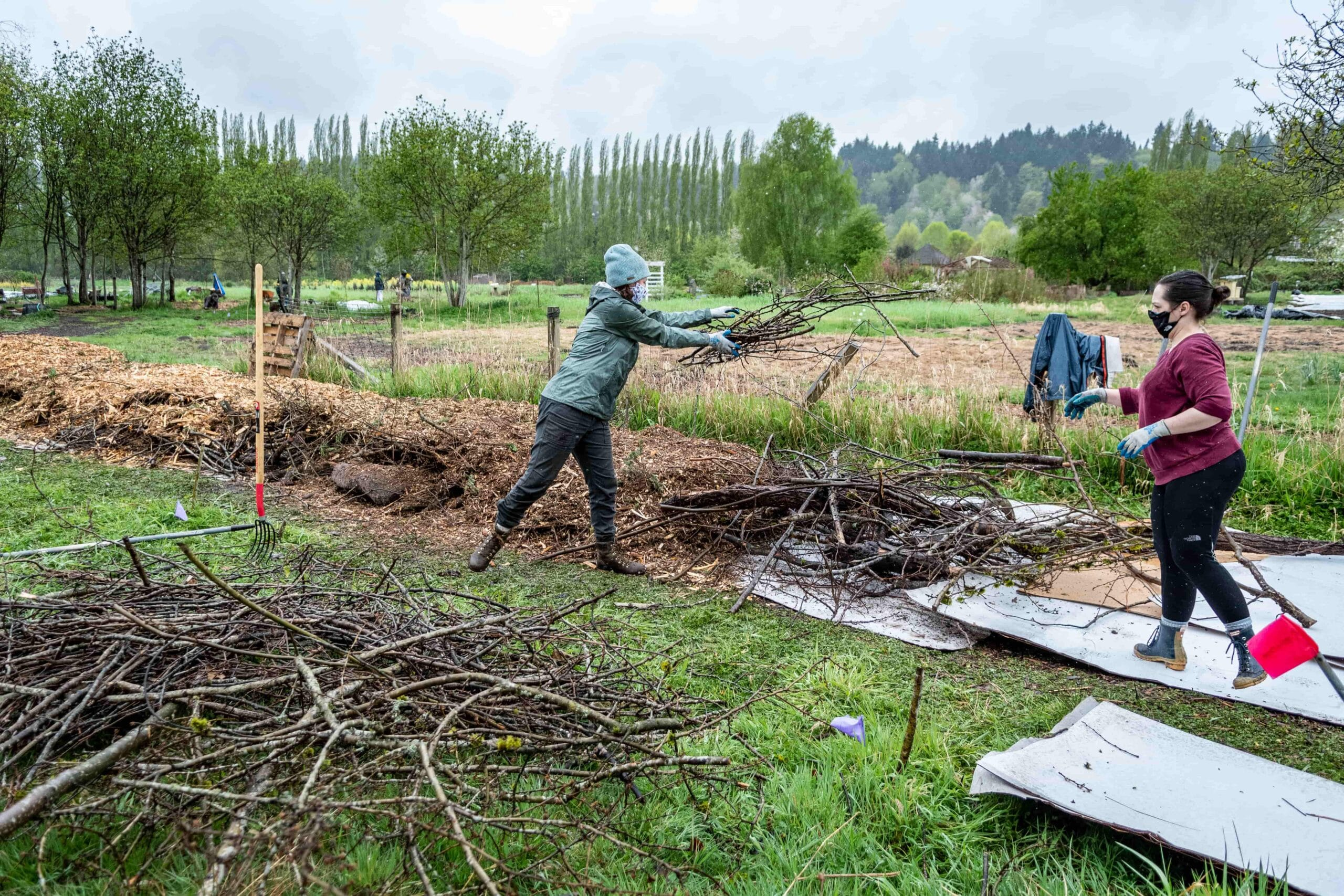 Volunteers build a hugel mound at the 21 Acres farm.