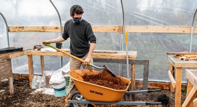 A farmer at 21 Acres shovels compost and other soil amendments in the greenhouse.