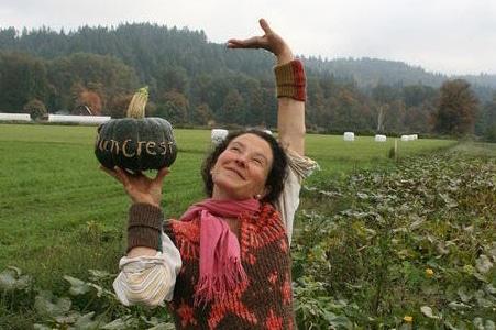 Alexia Allen of Hawthorn Farm holds a ripe squash aloft.